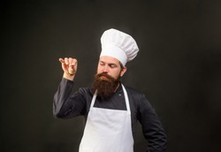 Handsome bearded chef in uniform spilling salt. Man chef in restaurant kitchen preparing food adding salt. Male chef sprinkling salt Bae. Cook man sprinkling salt. Ingredients. Professional kitchen.