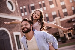 Handsome bearded dad and his cute little daughter are smiling while playing together outside, girl is sitting piggyback