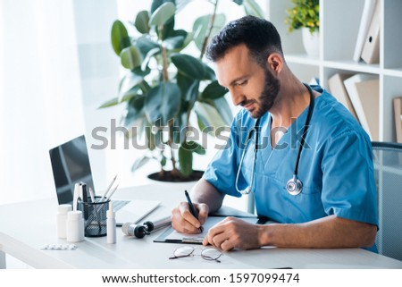 handsome bearded doctor writing diagnosis in clinic