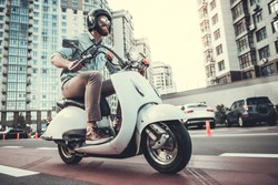 Handsome bearded guy in sun glasses and helmet is smiling while riding a scooter