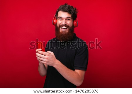 Handsome bearded guy, using a smartphone, and using headphones, looking at camera, standing over red background