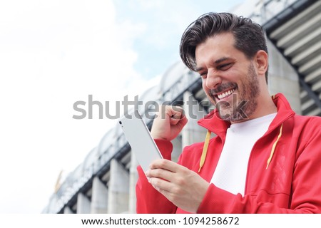 Handsome bearded hipster euphoric winner winning a betting and watching a smart phone with football stadium background. Man celebrate win a bet with a gambling mobile app. soccer bet, sports gambling. #1094258672