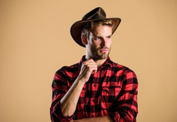 Handsome bearded macho. American cowboy. Beauty standard. Example of true masculinity. Cowboy wearing hat. Western life. Man unshaven cowboy beige background. Unshaven guy in cowboy hat.
