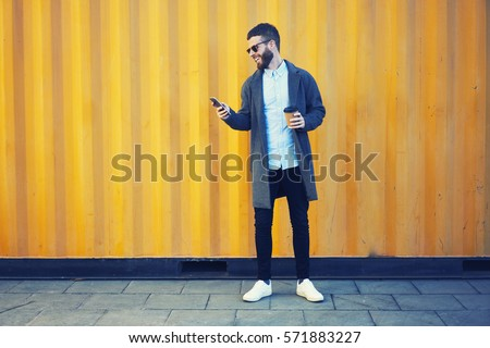 Handsome bearded male hipster making photo for blog sharing positive emotions feeling excited by sunny morning while walking to work with cup of coffee using modern smartphone and 4G internet #571883227