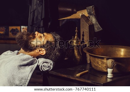 Handsome bearded man, hipster, brunette with beard and moustache has shave in barbershop. Vintage barber or shaver tools on wooden table