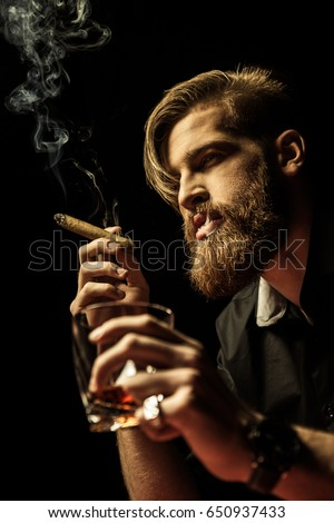 Handsome bearded man holding glass of whisky and smoking cigar on black