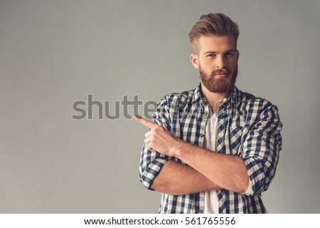 Handsome bearded man in casual clothes is pointing away, looking at camera and smiling, on gray background