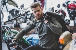 Handsome bearded man in motorcycle shop. Biker is choosing new vehicle and motorcycle accessories.