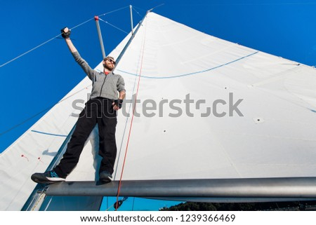 Handsome bearded man in sunglasses on a regatta standing on a sail boom