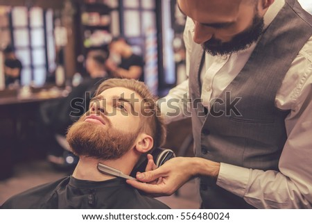 Handsome bearded man is getting shaved by hairdresser at the barbershop #556480024