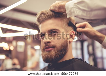 Handsome bearded man is smiling while having his hair cut by hairdresser at the barbershop #556479964