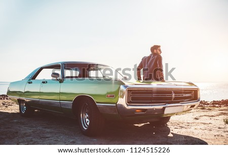 Handsome bearded man is standing near his green retro car on the beach. Vintage classic car. #1124515226
