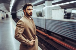 Handsome bearded man is waiting for train in subway.