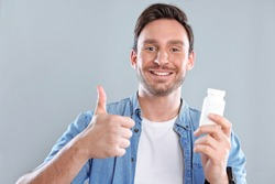 Handsome bearded man isolated on a white background with a bottle of pills. He trusts this medicine and he is happy because he wants to be healthy again.