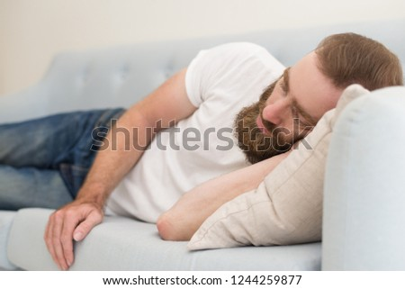 Handsome bearded man lying and dosing on sofa. Young guy dozing. Relaxation concept.