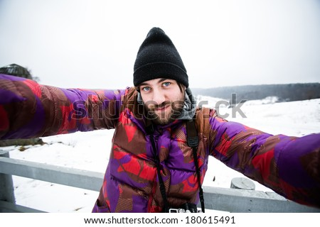 Handsome bearded man makes selfie in Russian forest in winter