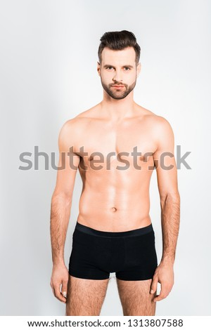 handsome bearded man posing in boxer shorts isolated on grey