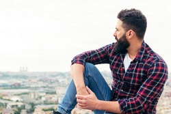 handsome bearded man sitting on the rooftop observing the city at his feet, concept of freedom and disconnection, copy space for text