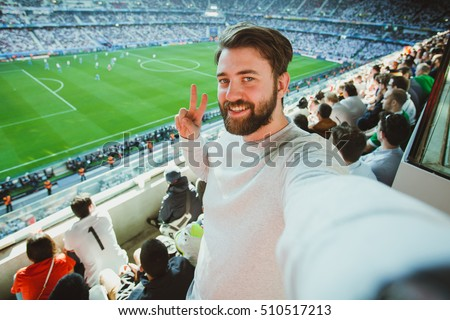 Handsome bearded man watching football game and making selfie self-portrait with smartphone at Camp Nou Stadium in Barcelona, Spain stock photo