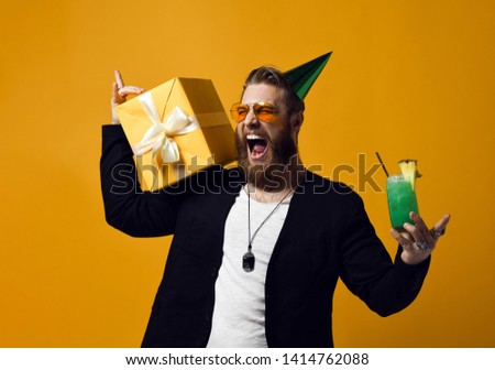 handsome bearded man with cone hat beard holding glass of cocktail and gift box celebrating birthday among friends isolated on yellow. Party