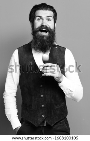 handsome bearded man with long beard and mustache on smiling face holding glass of alcoholic shot in vintage suede leather, waistcoat on red studio background