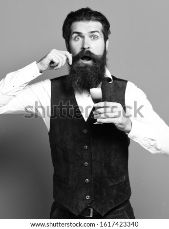handsome bearded man with long beard and mustache on surprised face holding glass of alcoholic shot in vintage suede leather waistcoat on red studio background
