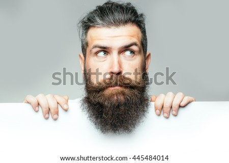 handsome bearded man with long lush beard and moustache on surprised face with white paper sheet in studio on grey background, copy space
