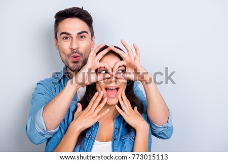Handsome bearded man with pout lips making eyewear with fingers to his wonderful girlfriend who holding her hands on face with open mouth looking side standing over grey background