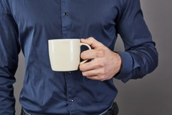 Handsome bearded man with stylish hair beard and mustache on serious face in shirt holding white cup or mug drinking tea or coffee in studio on grey background.