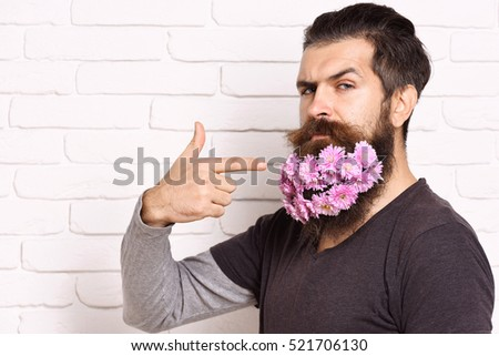 handsome bearded man with stylish mustache and shirt showing beard with pink autumn flowers on serious face on white brick wall background, copy space
