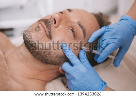 Handsome bearded mature man getting hyaluronic acid injection in his cheekbone at beauty salon. Mid-aged man receiving rejuvenating facial injections. Anti-wrinkle treatment #1394253026
