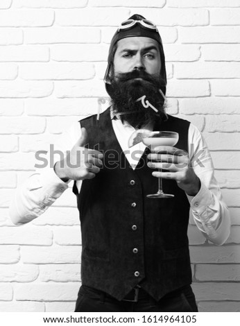 handsome bearded pilot man with long beard and mustache on serious face holding glass of alcoholic cocktail in vintage suede leather waistcoat with hat, and glasses on white brick wall background