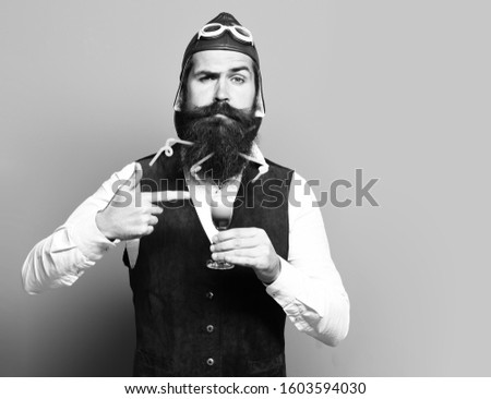 handsome bearded pilot or aviator man with long beard and mustache on funny face holding glass of alcoholic shot in vintage suede leather waistcoat with hat, and glasses on blue studio background