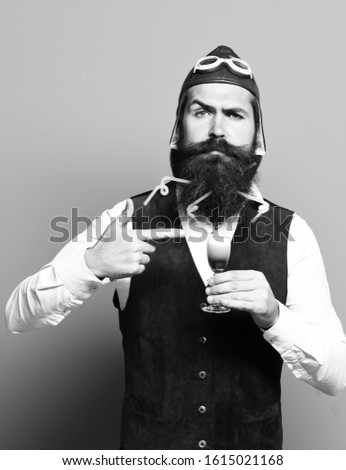 handsome bearded pilot or aviator man with long beard and mustache on funny face holding glass of alcoholic shot in vintage suede leather waistcoat with hat ,and glasses on blue studio background