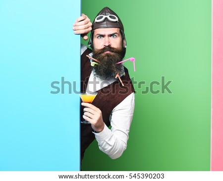 handsome bearded pilot or aviator man with long beard and mustache on funny face holding glass of alcoholic beverage in vintage suede leather waistcoat with hat and glasses on studio background