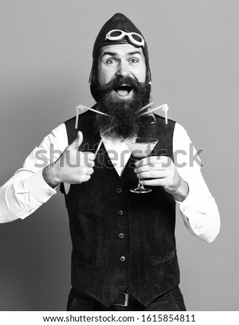 handsome bearded pilot or aviator man with long beard and mustache on happy face holding glass of alcoholic beverage in vintage suede leather waistcoat with hat, and glasses on red studio background