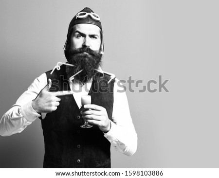 handsome bearded pilot or aviator man with long beard and mustache on serious face holding glass of alcoholic shot in vintage suede leather waistcoat with hat, and glasses on red studio background