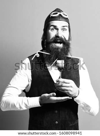 handsome bearded pilot or aviator man with long beard and mustache on smiling face holding glass of alcoholic shot in vintage suede leather waistcoat with hat, and glasses on red studio background