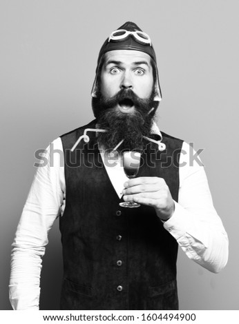 handsome bearded pilot or aviator man with long beard and mustache on surprised face holding glass of alcoholic shot in vintage suede leather waistcoat with hat, and glasses on blue studio background