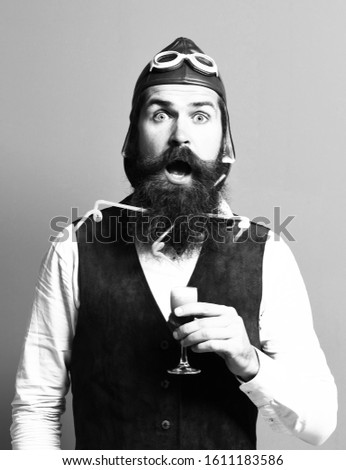 handsome bearded pilot or aviator man with long beard and mustache on surprised face holding glass of alcoholic shot in vintage suede leather waistcoat with hat, and glasses on red studio background