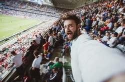 Handsome bearded supporter watching football game and making selfie self-portrait with smartphone at Camp Nou, Barcelona, Spain.