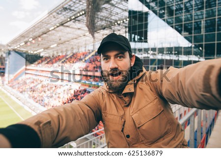 Handsome bearded supporter watching football game and making selfie self-portrait with smartphone at stadium. stock photo
