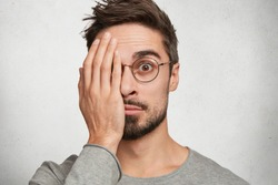 Handsome bearded young male covers eye with hands, looks through spectacles with wondering expression, afraid to see something, isolated over concrete white studio background. What is there?