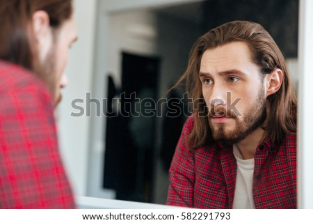 Handsome bearded young man in plaid shirt looking at the mirror at home