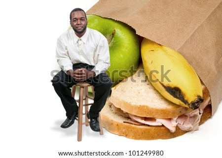 Handsome black African American man with a nutritious lunch in a brown bag.