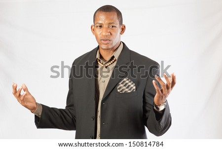 Handsome black businessman ina suit and tie, looking at the camera with a focused, serious expression, fists raised in a  posture of defense/offense