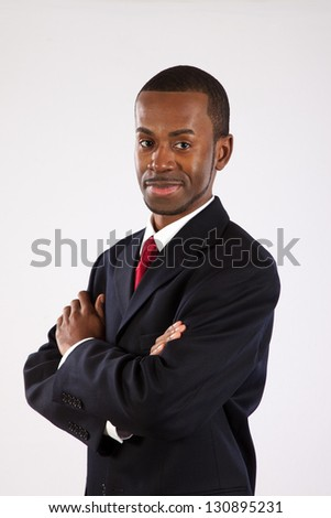 Handsome black businessman standing with his arms crossed confidently and looking at the camera with an assured smile