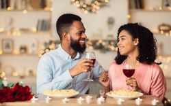 Handsome black man and pretty woman drinking wine at restaurant, toasting and celebrating Valentine's Day together. Couple of sweethearts having romantic dinner, enjoying festive meal in the evening