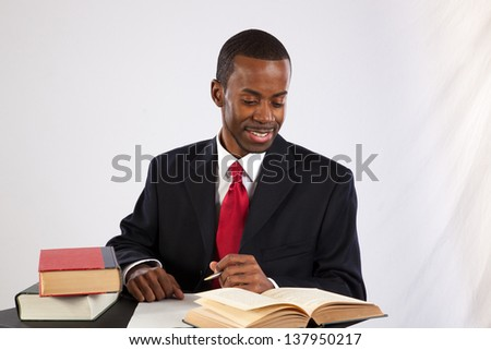 Handsome black man in a business suit, with books open before him, looking at the books with a thoughtful, pensive expression
