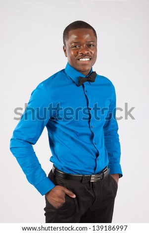 Handsome black man in bow tie and blue shirt, standing looking at the camera with his hands in his pockets